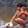 Bien temprano en la mañana una madre recoge agua para la familia.